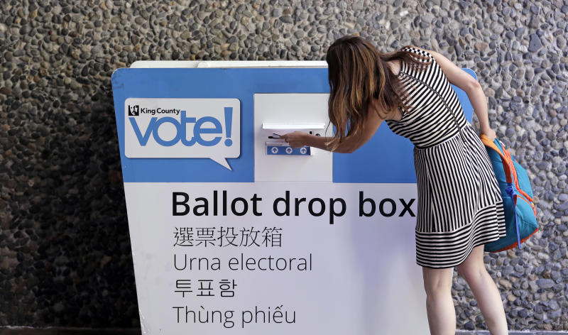A voter places her ballot into a drop box Tuesday, Aug. 7, 2018, in Seattle. Washington voters will decide which candidates advance to the November ballot in 10 congressional races, a U.S. Senate seat and dozens of legislative contests in the state's primary election Tuesday. (AP Photo/Elaine Thompson)