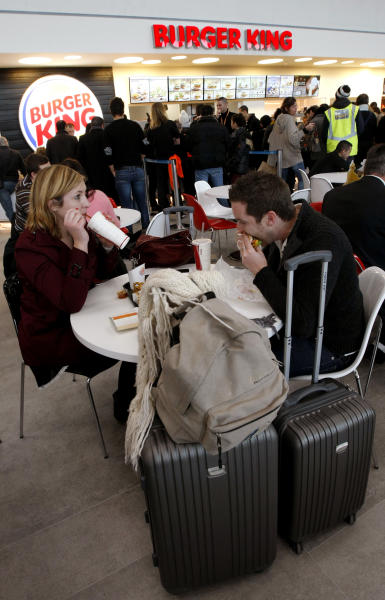 Customers eat a meal at a Burger King restaurant in Marseille-Provence airport, in Marignane, France, Saturday, Dec. 22, 2012. Fifteen years after leaving France, the U.S. hamburger chain Burger King returned with the opening of a restaurant in Marseille-Provence airport. (AP Photo/Claude Paris)