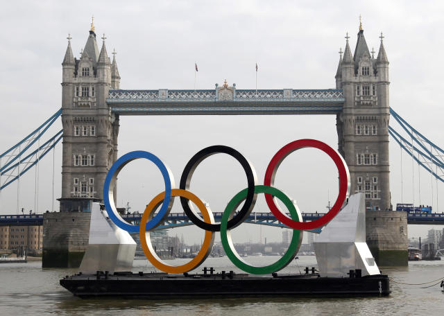 FILE - In this Feb. 28, 2012, file photo, a tug boat pulls a barge with giant Olympic rings that are 11 meters (36 feet) tall and 25 meters (82 feet) wide towards Tower Bridge as they are unveiled on the River Thames in London. If you miss any of your favorite events during the upcoming Summer Olympics in London, don't blame NBC. Every sport, every single competition will be streamed live online or telecast by NBC and its affiliated cable networks in the U.S. this summer _ starting with the Great Britain vs. New Zealand women's soccer game on July 25, two days before the opening ceremony. (AP Photo/Alastair Grant, File)