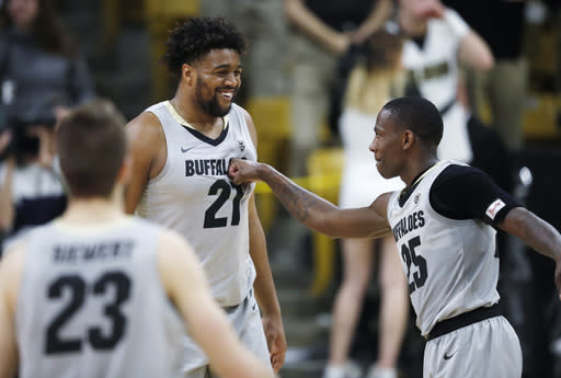 Colorado guard McKinley Wright IV, right, punches forward Evan Battey, left, while forward Lucas Siewert looks on as time runs out in the second half of an NCAA college basketball game against USC Saturday, March 9, 2019, in Boulder, Colo. Colorado won 78-67. (AP Photo/David Zalubowski)