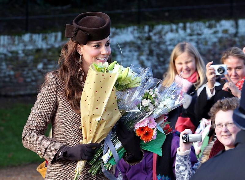 Catherine, Duchess of Cambridge, collects flowers from well-wishers at a Christmas Day church service near Sandringham on December 25, 2014.