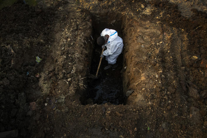 A man in protective suit digs earth to bury the body of a person who died of COVID-19 in Gauhati, India, Sunday, April 25, 2021. Delhi has been cremating so many bodies of coronavirus victims that authorities are getting requests to start cutting down trees in city parks, as a second record surge has brought India's tattered healthcare system to its knees. (AP Photo/Anupam Nath)