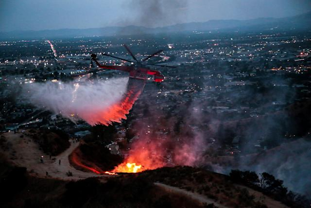 <p>Water is dropped above homes in Sun Valley during the La Tuna Canyon fire over Burbank, Calif., Sept. 2, 2017. (Photo: Kyle Grillot/Reuters) </p>