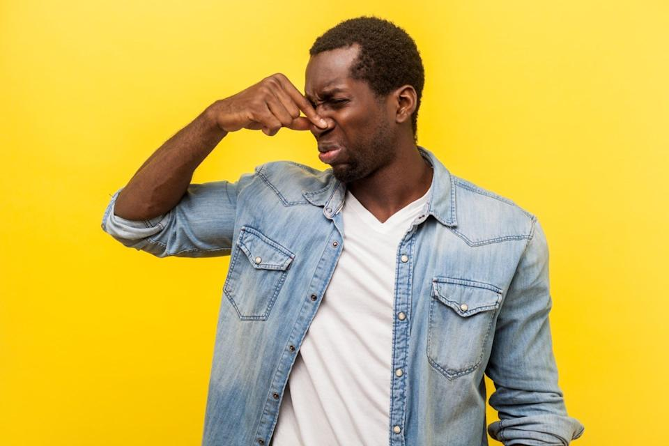 Unpleasant smell. Portrait of young man in denim casual shirt grimacing in disgust and pinching his nose, displeased by bad breath or stinky odor, fart. studio shot isolated on yellow background
