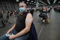 """Meti Gashi wears a sticker on his arm that reads, """"I got my COVID-19 vaccine at the Javits Center"""" as he waits during the observation period after getting his vaccine Thursday, March 18, 2021, in New York. For people on the road to immunity from the coronavirus, experiencing live music in the same space that served as a field hospital at the height of the pandemic was a fitting accompaniment on a day of hope. (AP Photo/Kathy Willens)"""