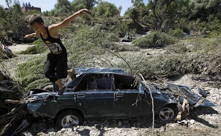 A child jumps from the a car stacked in mud on the bank of the river during flooding in the town of Nizhnebakansky, about 1,200 kilometers (750 miles) south of Moscow, Monday, July 9, 2012. Intense flooding in the Black Sea region of southern Russia killed at least 150 people after torrential rains dropped nearly a foot of water, forcing many to scramble out of their beds for refuge in trees and on roofs, officials said Saturday. (AP Photo/Sergey Ponomarev)