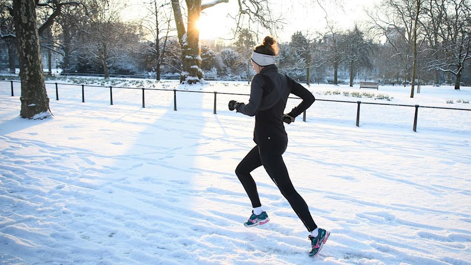 """LONDON, UNITED KINGDOM - FEBRUARY 28: A jogger runs through the snow in St James' Park on February 28, 2018 in London, United Kingdom. Freezing weather conditions dubbed the """"Beast from the East"""" brings snow and sub-zero temperatures to the UK. (Photo by Leon Neal/Getty Images)"""