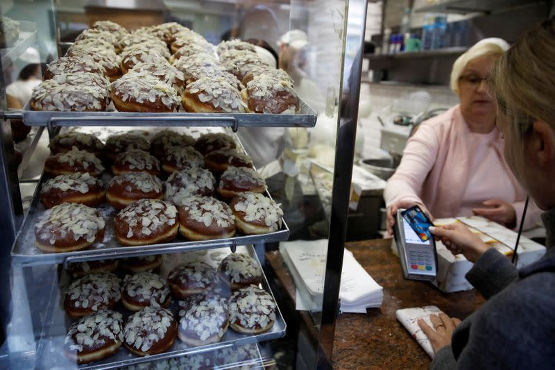 Woman buys doughnuts during traditional Fat Thursday when Poles eat doughnuts to mark the end of the carnival, at a bakery in Warsaw
