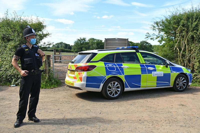 A police officer wearing a face mask at Rook Row Farm in Mathon, near Malvern, Herefordshire, where there have been 73 positive cases of coronavirus confirmed. (Photo: Jacob King/PA Wire )