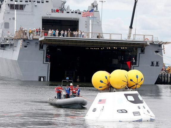 Divers attach tow lines to an Orion test spacecraft during a stationary recovery test at Norfolk Naval Base in August 2013.