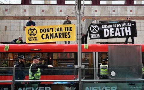 Climate change activists held up banners on the roof of a DLR train at Canary Wharf station - Credit: AFP
