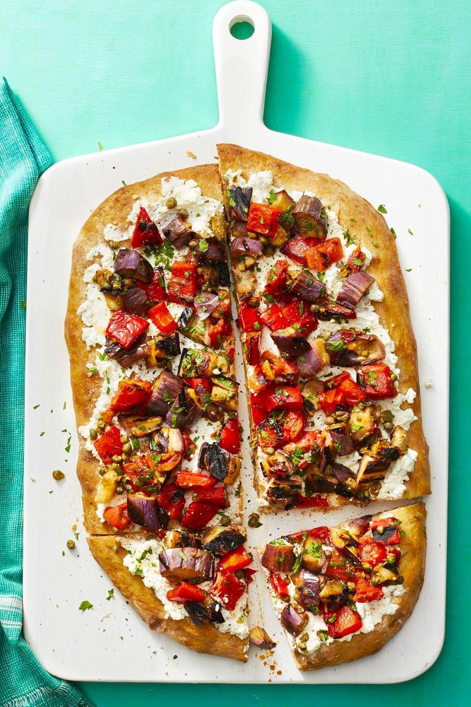 """<p>Combine capers and peppers for this sweet-and-sour pizza full of veggies.</p><p><a href=""""https://www.womansday.com/food-recipes/food-drinks/a22482763/caponata-flatbread-recipe/"""" rel=""""nofollow noopener"""" target=""""_blank"""" data-ylk=""""slk:Get the Caponata Flatbread recipe."""" class=""""link rapid-noclick-resp""""><em>Get the Caponata Flatbread recipe.</em></a></p>"""
