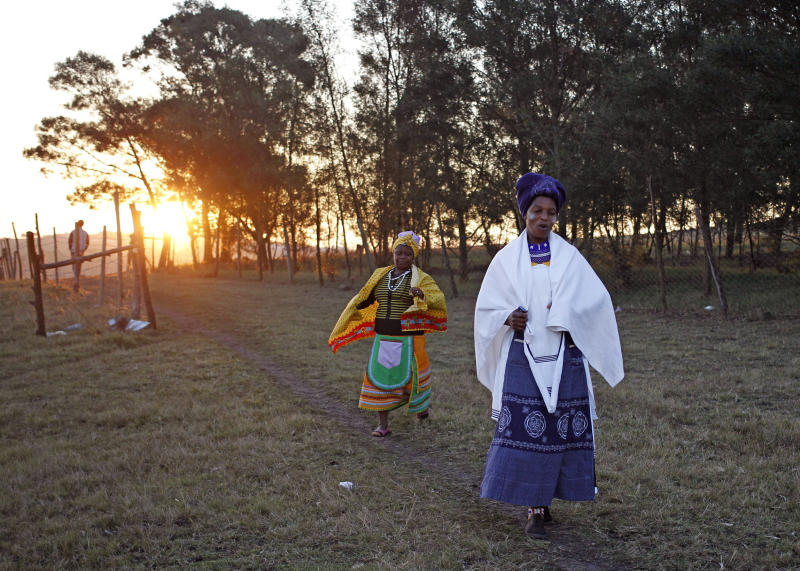 In this photo taken on Thursday, July 11, 2013, women arrive to celebrate the initiation ceremony of a relative near Qunu, South Africa. Initiation ceremonies in South Africa's Eastern Cape province have led to the deaths of more than 60 young men since May and the hospitalization of hundreds, sparking concern from government and health officials about the lack of regulation of a national tradition that determines when a boy becomes a man. (AP Photo/Schalk van Zuydam)