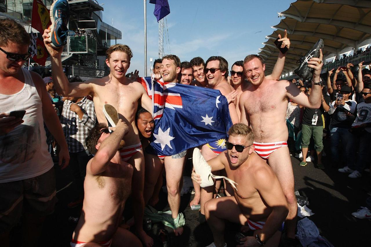 In this Sunday, Oct. 2, 2016 photo, Australian men pose for a photo in Budgy Smuggler-brand swimsuits decorated with the Malaysian flag at the conclusion of the Malaysian Formula One Grand Prix in Sepang, Malaysia. Malaysian authorities who have detained nine Australians for three nights would regard their actions in stripping down to their briefs and drinking beer from shoes as premeditated, Australia's foreign minister said Wednesday. (AP Photo)