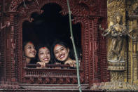 A former living goddess Kumari, center, watches the annual Indra Jatra festival in Kathmandu, Nepal, Sunday, Sept. 19, 2021. The feast of Indra Jatra marks the return of the festival season in the Himalayan nation two years after it was scaled down because the coronavirus pandemic. (AP Photo/Niranjan Shrestha)