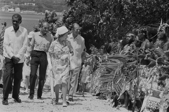 Men in traditional dress line the road during a visit by Queen Elizabeth (centre) and Prince Philip (centre, right) to Port Vila, Vanuatu, off the north-east coast of Australia, February 1974. (Photo by McCabe/Daily Express/Hulton Archive/Getty Images)