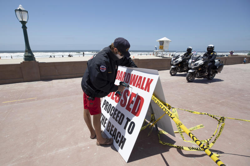 A San Diego lifeguard posts a sign along the closed beachfront boardwalk Friday, May 22, 2020, in San Diego. Millions of Californians are heading into the Memorial Day weekend with both excitement and anxiety after restrictions to control the spread of coronavirus were eased across much of the state. (AP Photo/Gregory Bull)
