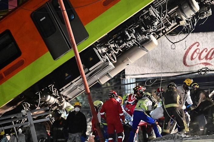 Rescue workers remove a body from a train carriage near a fallen Metro car.
