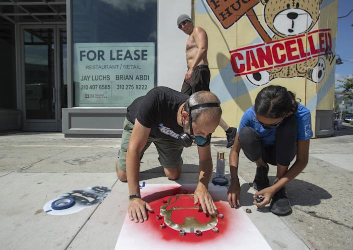 """Neal Brandenburg and daughter Ruby, 11, use nuts as weights to hold a stencil in position while creating an Iron Man-themed """"Heroes Wear Masks"""" drawing in Los Angeles. <span class=""""copyright"""">(Mel Melcon / Los Angeles Times)</span>"""