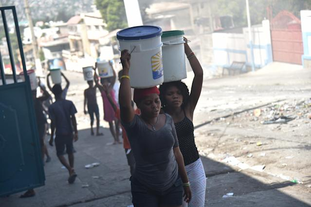 <p>Women carry buckets of water on a barricaded street in central Port-au-Prince, July 9, 2018, following two days of deadly looting and arson triggered by a quickly-aborted government attempt to raise fuel prices. (Photo: Hector Retamal/AFP/Getty Images) </p>