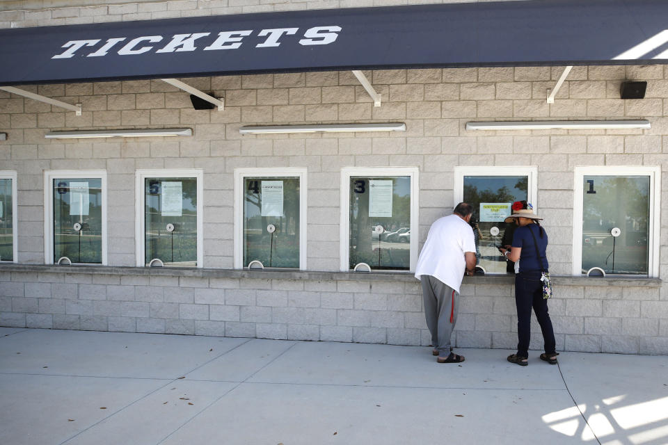 Baseball fans stand at the window for ticket refunds outside Hammond Stadium, Monday, March 16, 2020, in Fort Myers, Fla., after Major League Baseball suspended the rest of its spring training game schedule because of the coronavirus outbreak. Big league managers say that Major League Baseball has instructed them to prepare for spring training to start on time in mid-February despite uncertainty around the coronavirus. Tampa Bay Rays manager Kevin Cash said Wednesday, Dec. 16, 2020, that officials from the commissioner's office had a meeting with managers Tuesday an expressed optimism about opening spring camps as scheduled. (AP Photo/Elise Amendola)