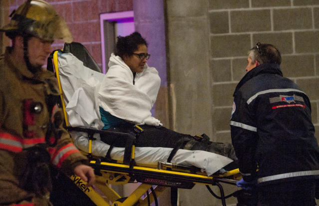 A woman who was trapped inside a wall of the parking garage is taken to an ambulance, Wednesday, Jan. 16, 2013 in Portland, Ore. Firefighters cut a hole through concrete and used an air bag and a soapy lubricant to free the woman. The woman spent about four hours in a space 8 to 10 inches wide before rescuers managed to free her as television cameras filmed much of the effort. Firefighters said they hadn't gotten a clear explanation of the woman's predicament. Lt. Rich Chatman of the Portland fire department, said she had been seen smoking or walking on the roof of a two-story building before she fell. (AP Photo/The Oregonian, Brent Wojahn) MAGS OUT; TV OUT; LOCAL TV OUT; LOCAL INTERNET OUT; THE MERCURY OUT; WILLAMETTE WEEK OUT; PAMPLIN MEDIA GROUP OUT