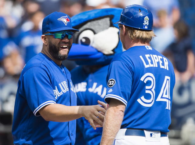 Toronto Blue Jays designated hitter Kendrys Morales, left, celebrates with first base coach Tim Leiper (34) after defeating the Baltimore Orioles in Toronto, Wednesday, Aug. 22, 2018. Morales homered for the fourth consecutive game, Thomas Pannone and two relievers combined on a two-hitter and the Blue Jays beat Baltimore 6-0. (Nathan Denette/The Canadian Press via AP)