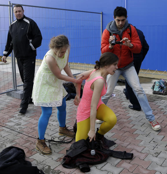 Maria Alekhina, second left, helps Nadezhda Tolokonnikova get up after they and other members of the punk group Pussy Riot were attacked by about a dozen Cossack militiamen outside a restaurant in downtown Sochi, Russia, about 30km (21miles) from where the Winter Olympics are being held, on Wednesday, Feb. 19, 2014. A plainclothes security official keeps an eye on the situation behind them. (AP Photo/Morry Gash)