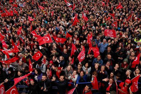Supporters of main opposition CHP wave flags as they listen to mayoral candidate Ekrem Imamoglu during a gathering in Istanbul