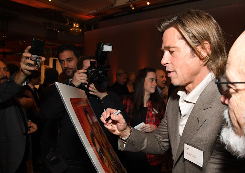 US actor Brad Pitt signs a poster during the 2020 Oscars Nominees Luncheon at the Dolby theatre in Hollywood on January 27, 2020. (Photo by Robyn BECK / AFP) (Photo by ROBYN BECK/AFP via Getty Images)