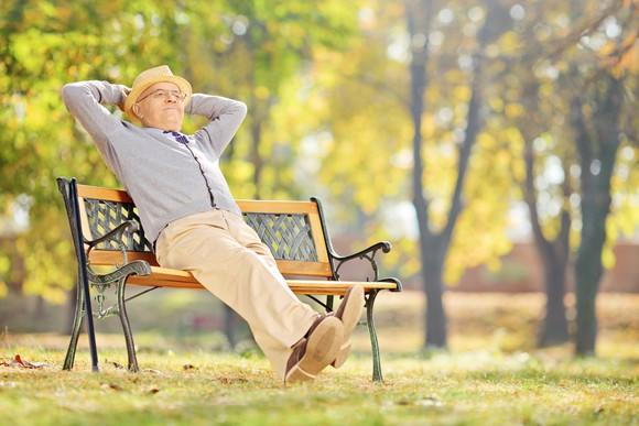An aged gentleman resting in a park.