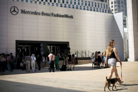 A woman walks her dog outside the tents at the Spring/Summer 2015 New York Fashion Week at Lincoln Center