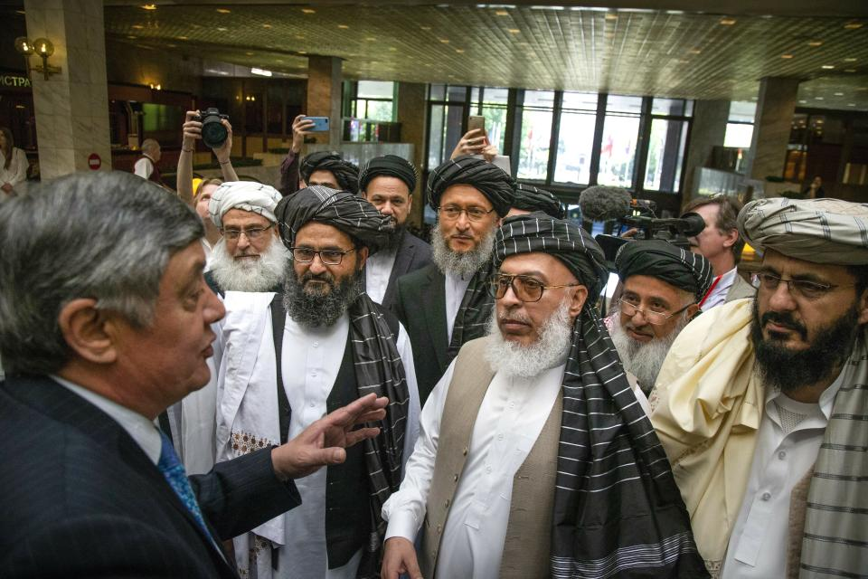 FILE - In this file photo taken on Tuesday, May 28, 2019, Russian presidential envoy to Afghanistan Zamir Kabulov, left, speaks to Mullah Abdul Ghani Baradar, the Taliban group's top political leader, third left, Sher Mohammad Abbas Stanikzai, the Taliban's chief negotiator, third right, and other members of the Taliban delegation prior to their talks in Moscow, Russia. With talks between the Afghan government and the Taliban stalled and Washington reviewing its options, Russia has stepped up its diplomatic efforts to push peace in Afghanistan making the rounds of regional players, including in Pakistan on Friday, as well as meeting Taliban and senior Afghan officials. (AP Photo/Alexander Zemlianichenko, File)