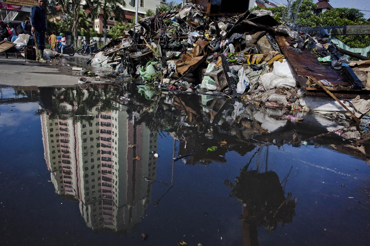 JAKARTA, INDONESIA - JANUARY 26:  Workers clean up waste that was piled up by the flood at Pakin river in North Jakarta on January 26, 2013 in Jakarta, Indonesia. With heavy rain forecast for January 26-28, Indonesian authorities have organised the use of generators and cloud-seeding measures to defuse rain-laden clouds to help prevent further flooding of Jakarta, following last week's floods which claimed the lives of 32 people.  (Photo by Ulet Ifansasti/Getty Images)