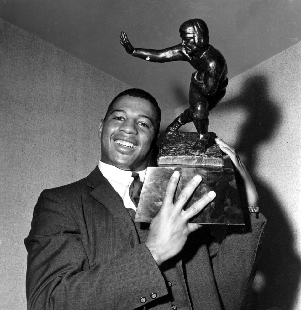 FILE - Ernie Davis, halfback for Syracuse, holds the Heisman Trophy prior to official presentation to him in New York City, in this Dec. 6, 1961, file photo. Syracuse was one of the standard-bearers in terms of accepting athletes based on performance and ability. Its history includes: Wilmeth Sidat-Singh, a quarterback and the first star Black athlete at the school in the 1930s; Bernie Custis, who quarterbacked the Orange from 1948-50 and became the first Black professional quarterback in the modern era with the Hamilton Tiger-Cats of the Canadian Football League; Jim Brown, regarded by many as the greatest running back of all time, starred at Syracuse in the mid-1950s and has dedicated much of his life to issues of social justice; and former Orange tailback Ernie Davis, the first Black to win the Heisman Trophy (1961). (AP Photo/File)