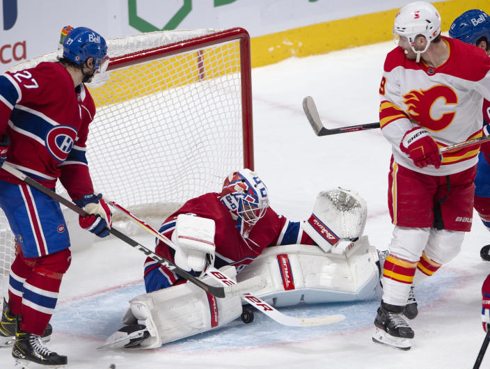 Montreal Canadiens goaltender Jake Allen (34) makes a save as Calgary Flames' Matthew Tkachuk, right, and Montreal Canadiens Alexander Romanov, left, look on during the second period of an NHL hockey game Wednesday, April 14, 2021 in Montreal. (Ryan Remiorz/Canadian Press via AP)