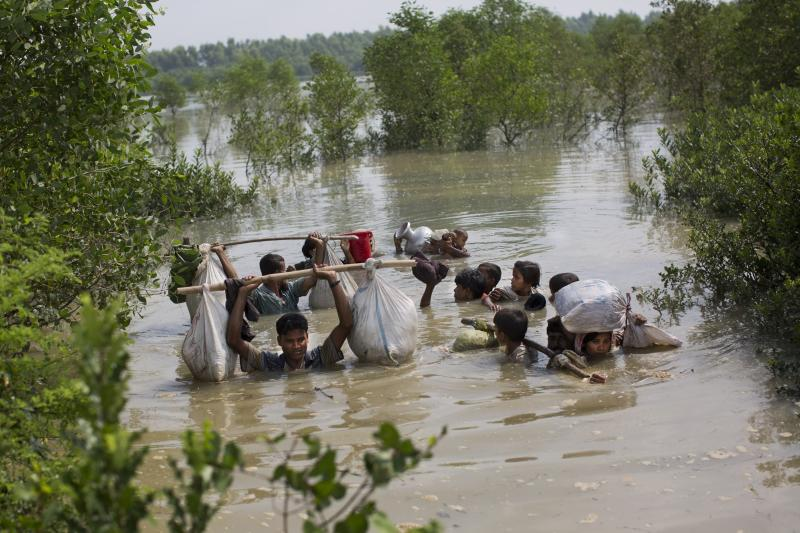 """-FILE- In this Tuesday, Sept. 5, 2017, file photo a Rohingya family reaches the Bangladesh border after crossing a creek of the Naf river on the border with Myanmmar, in Cox's Bazar's Teknaf area. Gambia has filed a case at the United Nations' highest court in The Hague, Netherlands, Monday, Nov. 11, 2019, accusing Myanmar of genocide in its campaign against the Rohingya Muslim minority. A statement released Monday by lawyers for Gambia says the case also asks the International Court of Justice to order measures """"to stop Myanmar's genocidal conduct immediately."""" (AP Photo/Bernat Armangue, file)"""