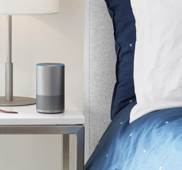 An Amazon Echo sitting on a nightstand.
