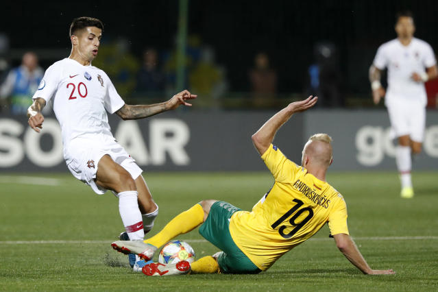 Portugal's Joao Cancelo, left, fights for the ball with Lithuania's Vytautas Andriuskevicius during the Euro 2020 group B qualifying soccer match between Lithuania and Portugal at LFF stadium in Vilnius, Lithuania, Tuesday, Sept. 10, 2019. (AP Photo/Mindaugas Kulbis)