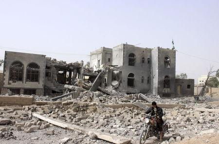 A man rides a motorcycle past a headquarters of the Houthi group, which was destroyed after an air strike by a Saudi-led coalition, in Yemen's northwestern city of Saada April 26, 2015. REUTERS/Stringer