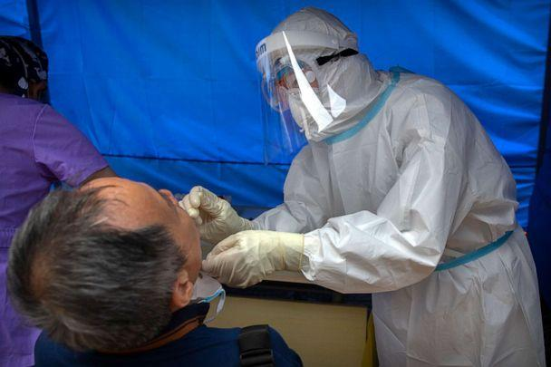 PHOTO: A worker wearing a protective suit swabs a man's throat for a COVID-19 test at a community health clinic in Beijing, China, on June 28, 2020. (Mark Schiefelbein/AP)