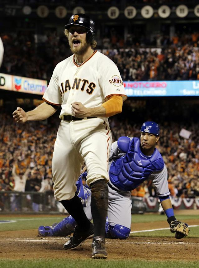 Kansas City Royals catcher Salvador Perez watches as San Francisco Giants' Hunter Pence celebrates after scoring on a double by Juan Perez during the eighth inning of Game 5 of baseball's World Series Sunday, Oct. 26, 2014, in San Francisco. (AP Photo/David J. Phillip)