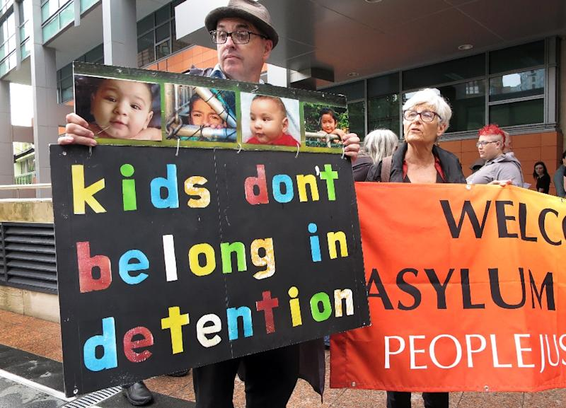 People hold placards at a protest outside an immigration office in Sydney, in February 2016 (AFP Photo/William West)