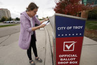 FILE - In this Thursday, Oct. 15, 2020 file photo, Nikki Schueller inserts her absentee voter ballot into a drop box in Troy, Mich. Just days before the presidential election, millions of mail-in ballots have still not been returned in key battleground states. Many of those are due in county offices by Tuesday, Nov. 3, but the latest Postal Service delivery data suggests it's too late for voters to drop their ballots in the mail. (AP Photo/Paul Sancya, File)