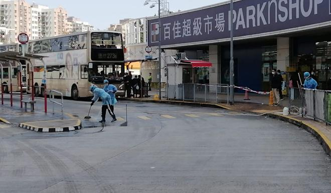 Workers in protective gear sanitise the area around a bus terminal where an elderly man who fled quarantine was intercepted on February 18. Photo: Handout