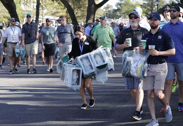 Patrons carry souvenirs as they attend practice for the 2018 Masters golf tournament at Augusta National Golf Club in Augusta, Georgia, U.S. April 2, 2018. REUTERS/Jonathan Ernst