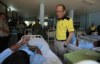 Philippine President Benigno Aquino (R) talks to a soldier wounded in clashes with Abu Sayyaf militants, at a military hospital in Zamboanga City, Mindanao on April 13, 2016