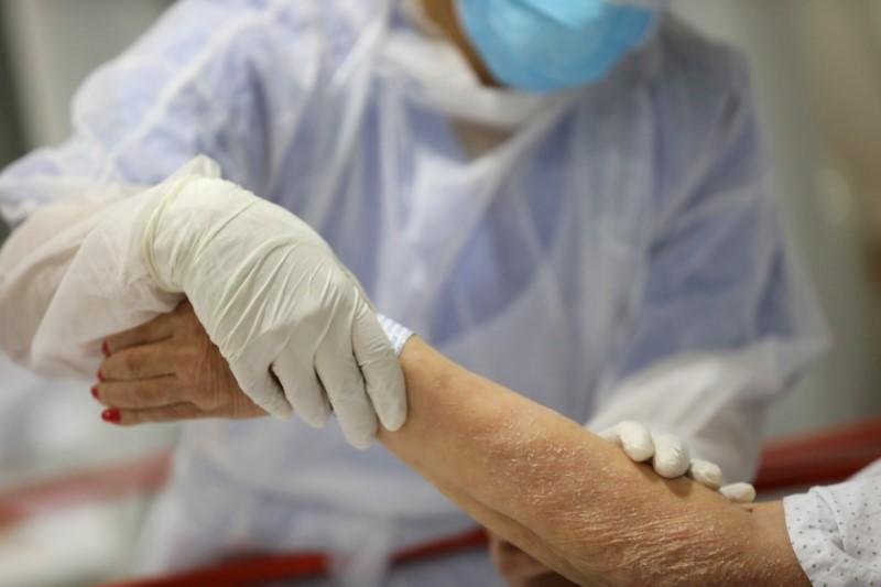 FILE PHOTO: A healthcare worker treats an elderly patient at the emergency room as the spread of the coronavirus disease (COVID-19) continues, at Infanta Sofia University hospital in Madrid