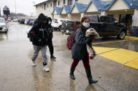 A family arrives at a Gallery Furniture store which opened as a shelter Wednesday, Feb. 17, 2021, in Houston. Millions in Texas still had no power after a historic snowfall and single-digit temperatures created a surge of demand for electricity to warm up homes unaccustomed to such extreme lows, buckling the state's power grid and causing widespread blackouts. (AP Photo/David J. Phillip)