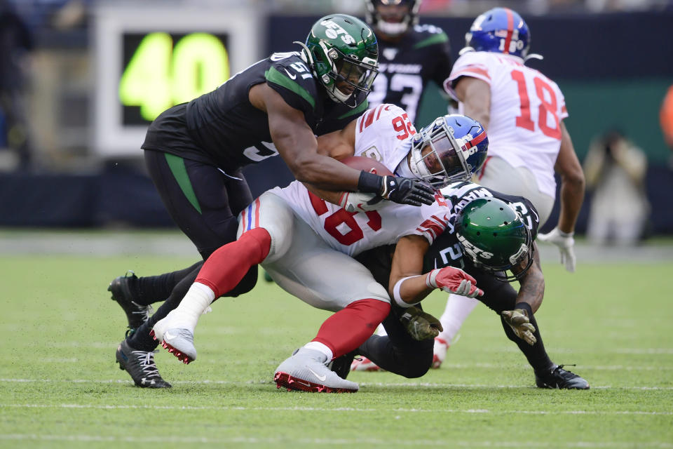 New York Jets' Brandon Copeland (51) and Arthur Maulet (23) tackle New York Giants' Saquon Barkley (26) during the second half of an NFL football game Sunday, Nov. 10, 2019, in East Rutherford, N.J. (AP Photo/Steven Ryan)
